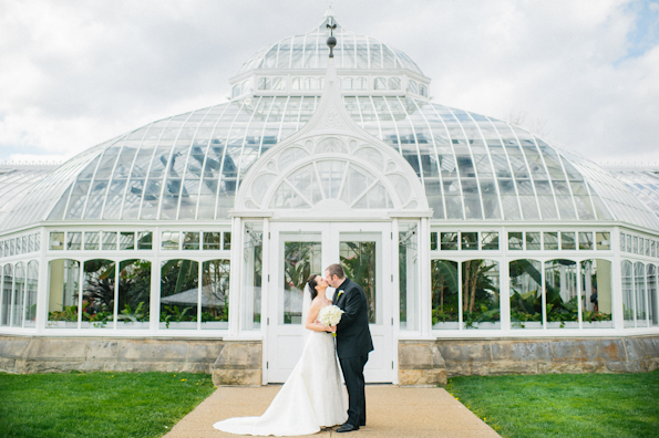 Bride and groom pose in front of a huge glass green house in the Oakland area of Pittsburgh, PA USA