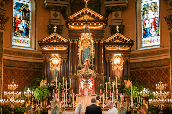 Bride and groom stand before the alter during their catholic ceremony in Polish Hill, Pittsburgh PA
