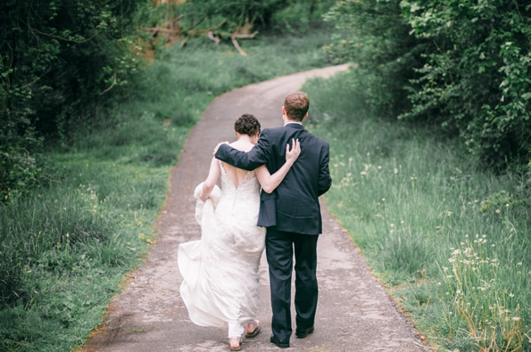 Bride and groom walk away as they hold each other tightly