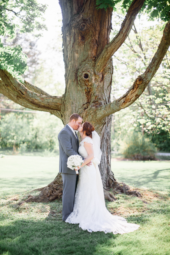 bride wears beautiful lace wedding dress while groom wears a gray wedding suit