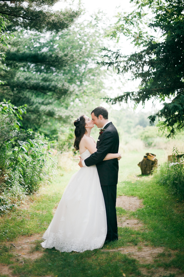Bride and groom stand in the middle of the woods in a fairytale setting for portraits