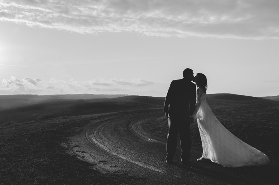 bride and groom kiss on top of a mountain