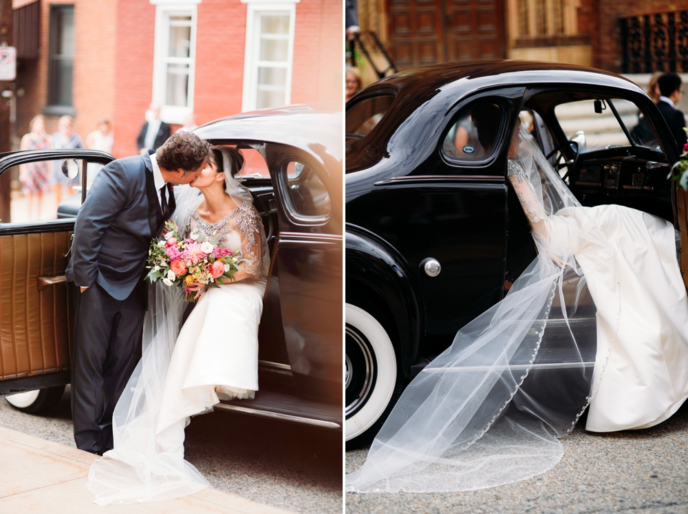 Bride and groom kiss in classic black car
