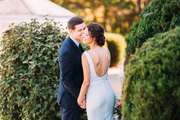 bride and groom cuddle in a low cut back wedding gown