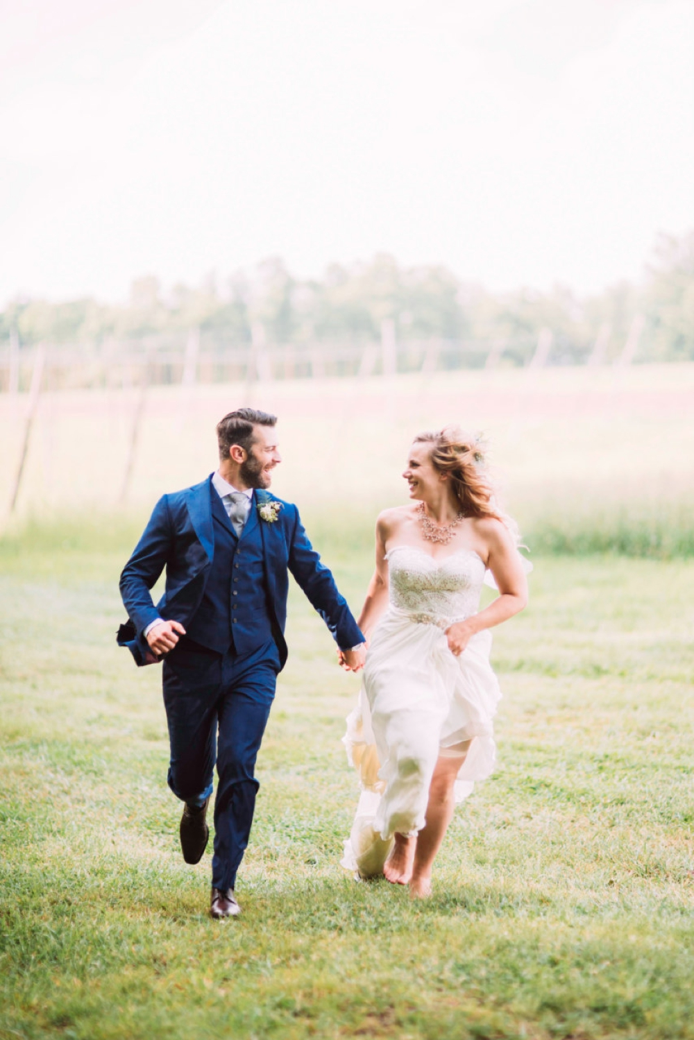 Bride and groom running in a field