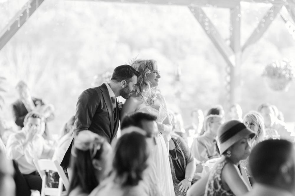 Groom kisses brides shoulder during toasts
