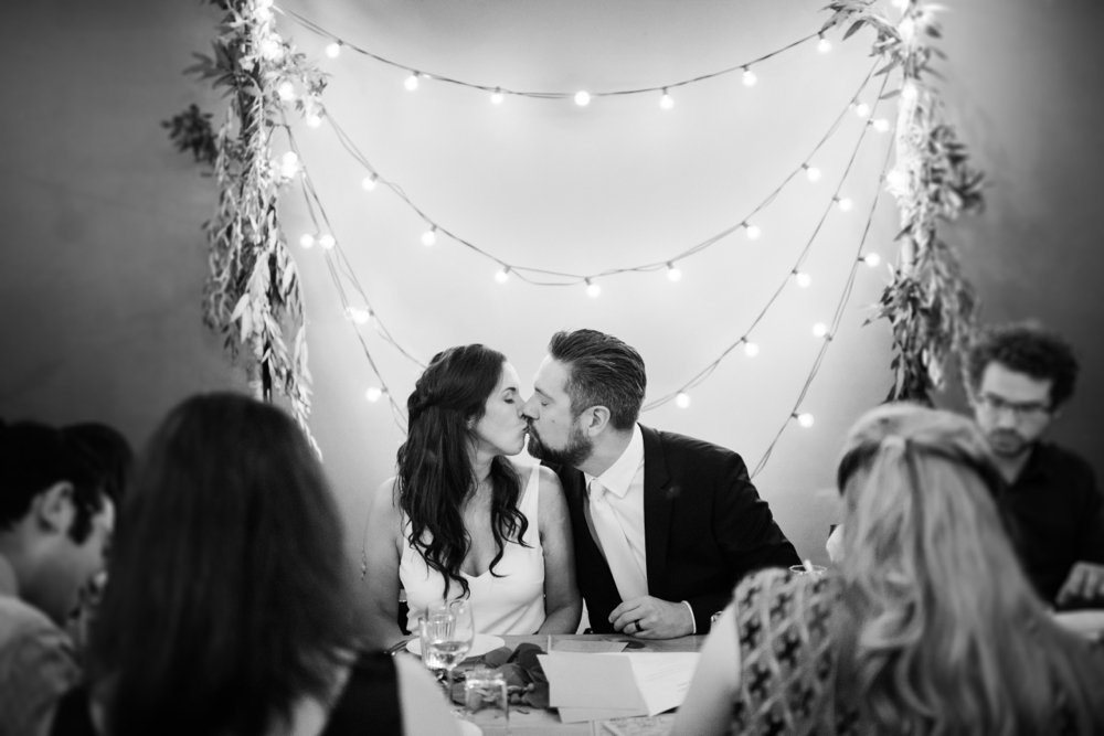Bride and groom kiss in front of string lights