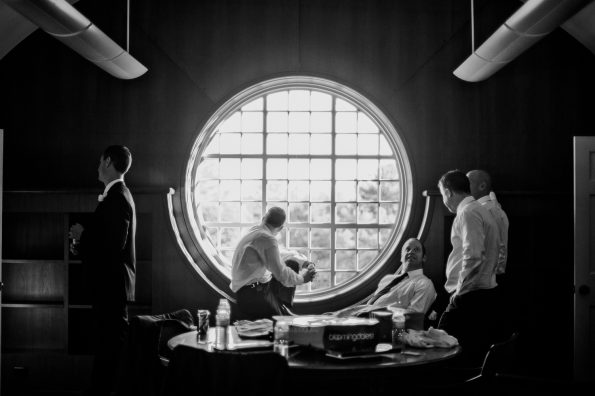 groomsmen hanging out in front of a large window