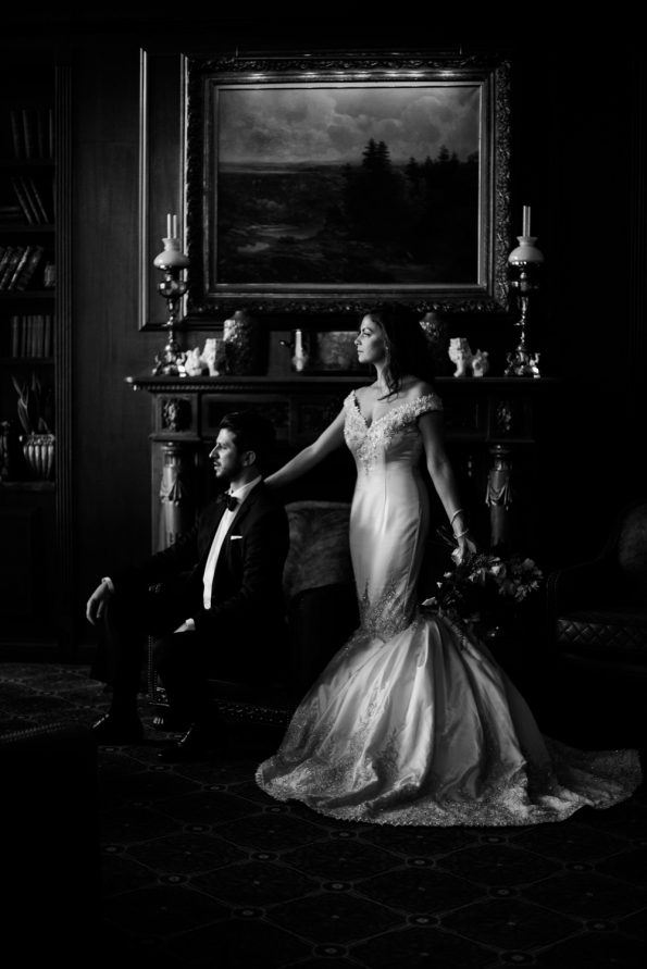 bride and groom posing in cigar room at elegant venue