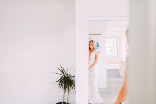 bride looking in the mirror waiting for her father to see her
