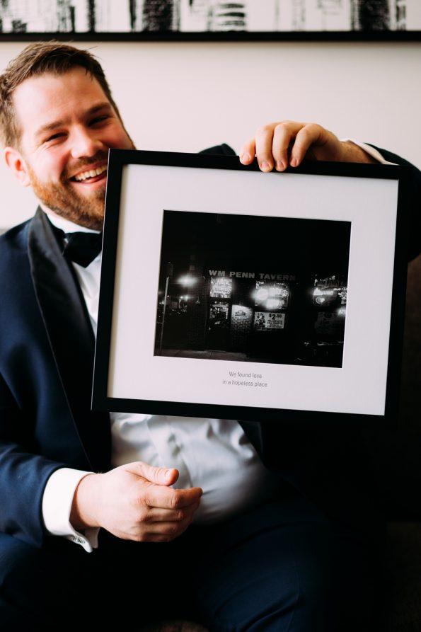 Groom holding framed portrait