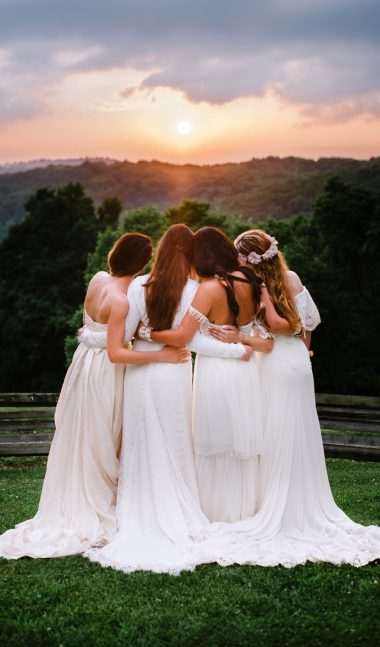 Brides and bridesmaids hugging and looking into sunset