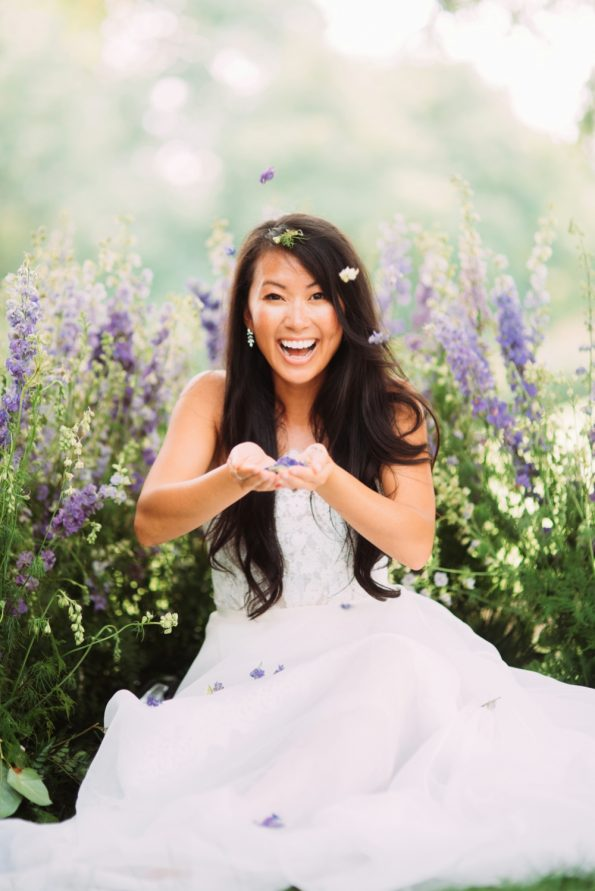 bride blowing flowers toward camera