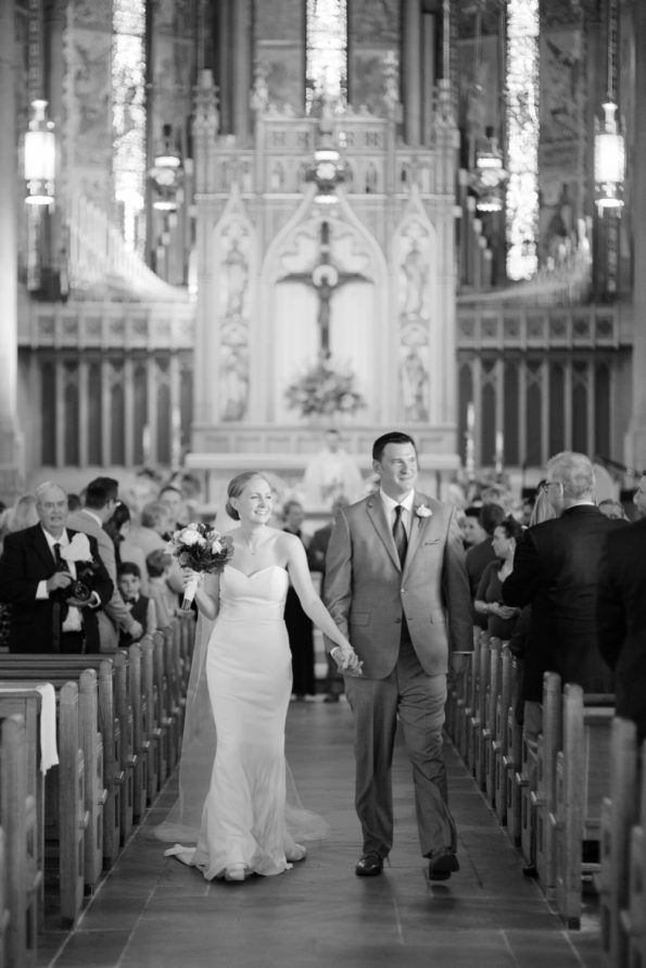 Bride and groom walking down aisle in cathedral